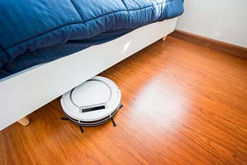 Robot aspiradora limpiando bajo una cama